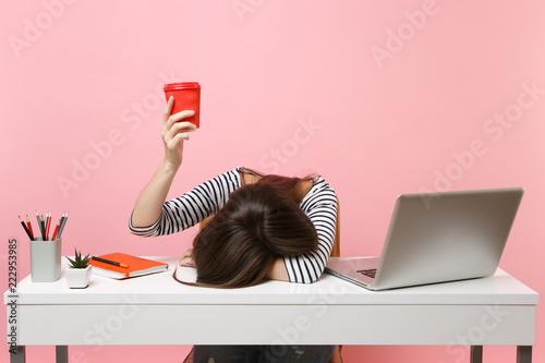 Fotografiet Exhausted woman laid her head down on the table holding cup of coffee or tea sit, work at white desk with pc laptop isolated on pastel pink background