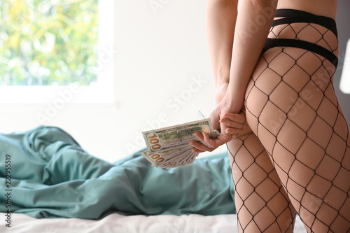 Young prostitute with money in brothel