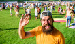 Leinwandbild Motiv Man bearded hipster in front of crowd people green field background. Hipster in cap visiting social event picnic fest or festival. Urban event celebration. Man waving hand sunny day outdoors