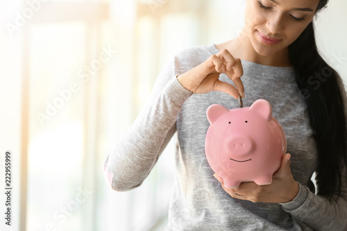Fotografía  Young woman putting money into piggy bank near window