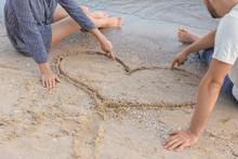Cute Young Couple Near Heart Drawn On Beach Sand