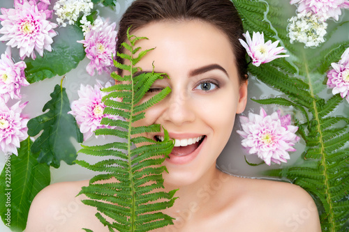 Fotografia  Portrait of young sexy beauty female woman smiling with clean pure skin taking spa relaxing in bath with flowers and green leafs white soap water
