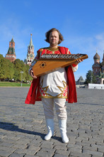Musician With Music Instrument Gusli Standing On Red Square