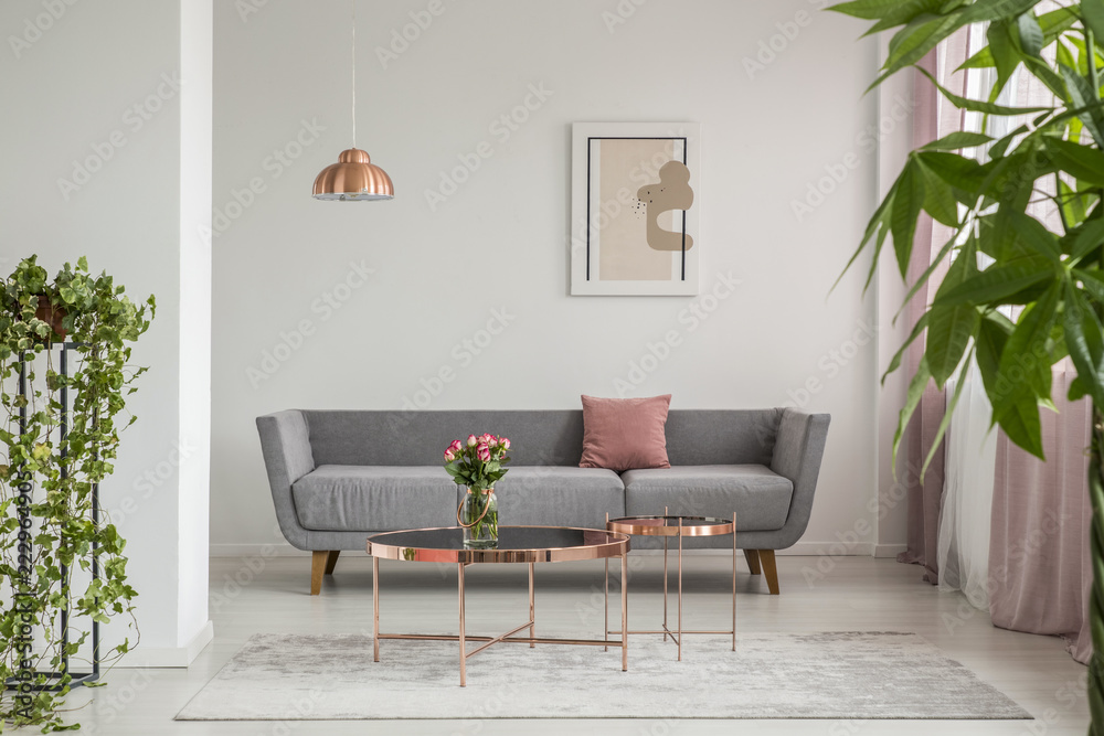 Fototapety, obrazy: Close-up of leaves in an elegant living room interior with a grey couch and copper tables decorated with roses. Real photo