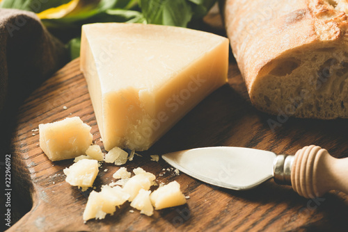 Parmesan cheese and cheese knife on wooden board. Toned image, selective focus