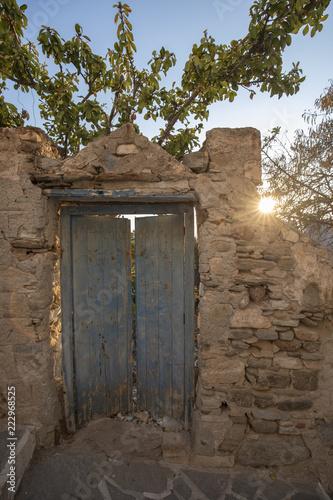 Valokuva  Verfallene Holztür im Mauerwerk mit Sonne im Gegenlicht