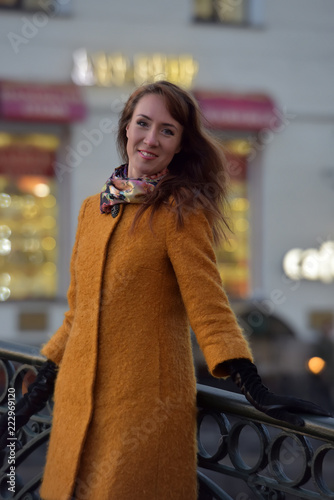 Fotografía  Elegant woman in the orange autumn coat on a background of the embankment of the