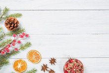 Christmas Background. Fir Tree Branches With Dried Orange, Anise Stars, Christmas Ball And Cone On White Wooden Background. Top View With Copy Space For Your Text