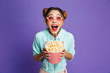 canvas print picture - Photo of european girl 20s in sunglasses laughing and holding bucket with popcorn, isolated over violet background in studio