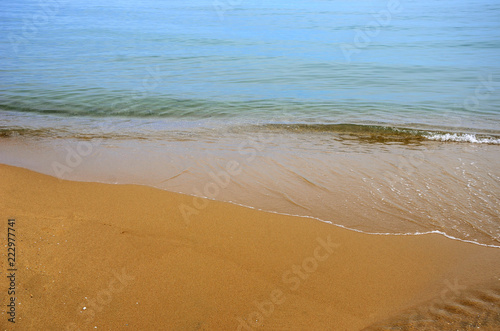 Wet sand on the beach. A part of the sea is visible.