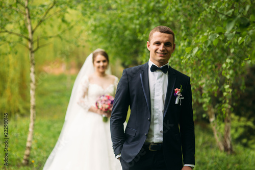 Billede på lærred The newlyweds are walking in the park on the wedding day