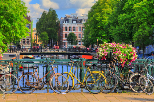 Beautiful vibrant summer flowers and bicycles on a bridge on the famous world heritage canals of Amsterdam, The Netherlands