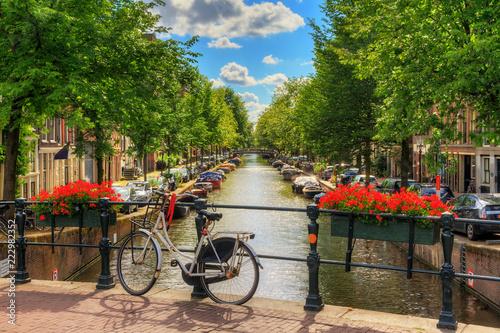 Fototapeta premium Piękne, żywe letnie kwiaty i rower na moście nad słynnymi kanałami światowego dziedzictwa w Amsterdamie w Holandii