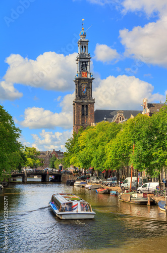 Canalboat tour at the UNESCO world heritage Prinsengracht canal with the Westerkerk (Western church) on a sunny summer day with blue sky and clouds