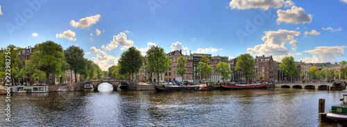 Beautiful panoramic panorama of the river Amstel in Amsterdam, the Netherlands, on a sunny summer day with some clouds