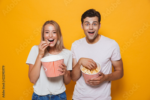 Photo  Happy young couple standing isolated over yelow