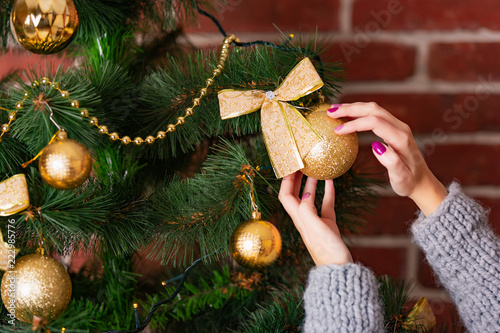 Fotobehang Bomen woman's hands adorn Christmas tree by golden toy with a bow-knot on the background of wall with bricks in the room in the winter. Close-up