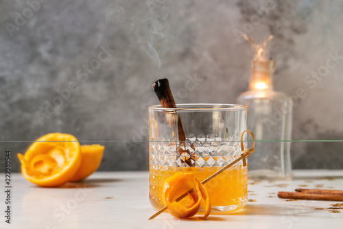 Foto op Canvas Cocktail Glass of Scotch Whiskey orange juice alcohol cocktail with swirled orange peel and smoking cinnamon sticks standing on white marble table with golden holiday Christmas stars confetti and sparkler.