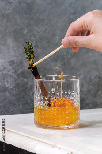 Glass of Scotch Whiskey orange juice alcohol cocktail with swirled orange peel on skewer, thyme and cinnamon sticks set fire to match, on white marble table with grey wall at background.