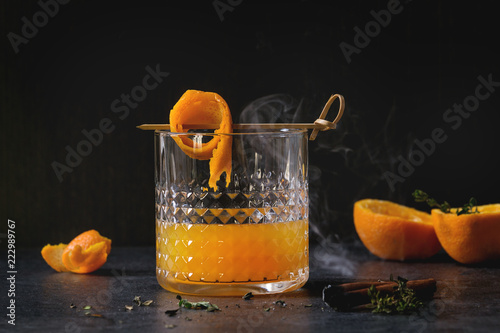 Foto op Canvas Cocktail Glass of Scotch Whiskey orange juice alcohol cocktail with swirled orange peel on skewer, thyme and smoking cinnamon sticks standing on black marble table.