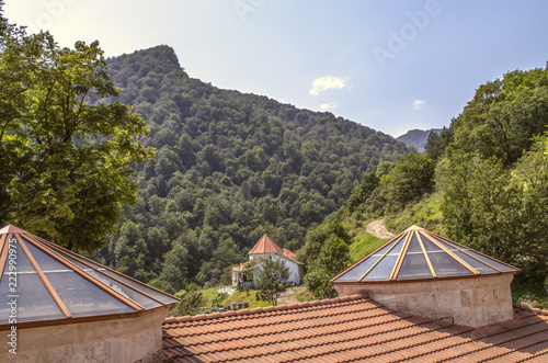 Restored roof of the refectory with domes with built-in glazed frames in the monastery of Agartsin,surrounded by forest near Dilijan