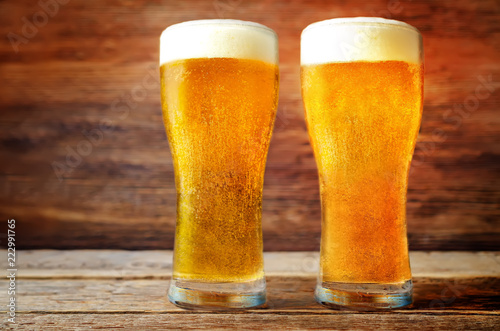 Foto op Aluminium Bier / Cider Glasses of cold light beer on a wood background. toning. selective focus