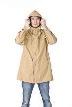 Young Guy Wearing In Raincoat Keeping His Hood By Hands