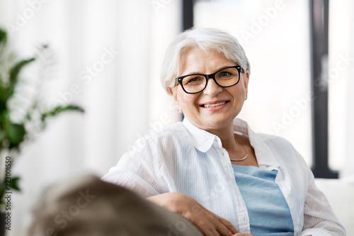 Fotografia  vision, age and people concept - portrait of happy senior woman in glasses sitti