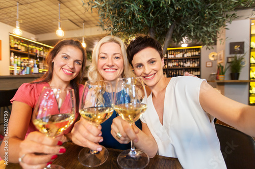 Foto people, technology and lifestyle concept - women drinking wine and taking selfie