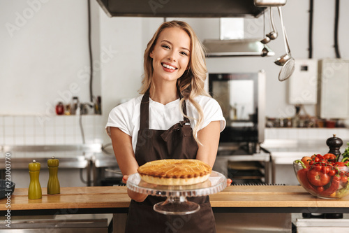 Photo  Smiling young woman chef cook in apron