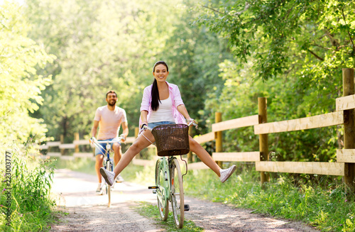 cycling, leisure and lifestyle concept - happy young couple with bicycles at sum Fototapeta