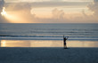 Unidentifiable african american woman relaxing at Jacksonville beach, looking at the sun going up at the sea. Beatiful sunrise