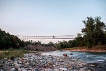 Traveller Walks The Bridge Over River