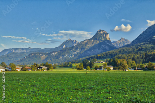 HDR beautiful landscape with lush green grass land and Alpine mountains near Wolfgangsee lake in Austria.