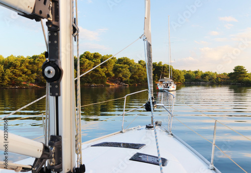 The mainmast is a mast and a twirled staysail on a sailing yacht and bow rails against the backdrop of a picturesque green bay with a yacht anchored Fototapet