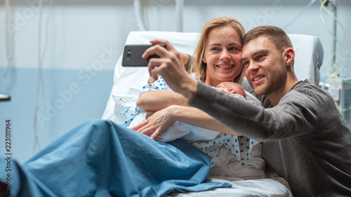 Father Takes Selfie of Him with His Wife Holding Newborn Baby while Lying on the Hospital Bed Fototapet