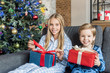 cute happy kids in pajamas holding presents and smiling at camera at christmas time