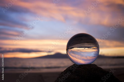 Pink Clouds at Sunset over Ocean with Island Captured in Glass Ball Wallpaper Mural