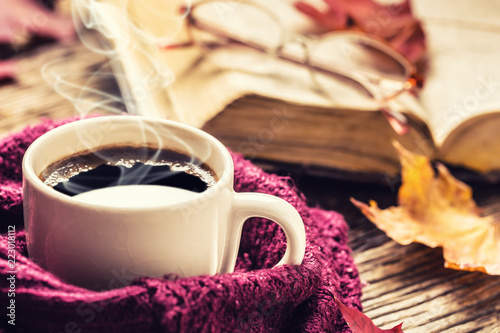 Tuinposter Herfst Cup of coffee old book glasses and autumn leaves.