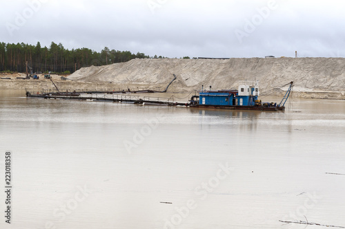 The dredger extracts sand from the quarry in the forest. Fototapet