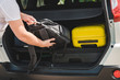 hands load bags in car trunk