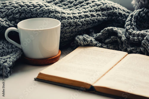 Stickers pour porte The woolen scarf, a cup of tea and book on the windowsill. Hygge and cozy autumn concept