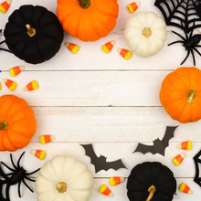 Halloween Frame With Black, Orange And White Decor And Candy Over A White Wood Background. Top View With Copy Space.