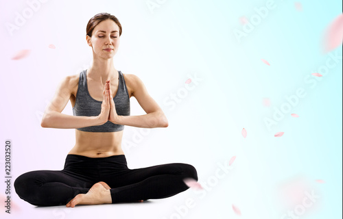 Young woman practicing yoga in lotus position.