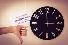 Big Black Clock On White Wall. Time Change. DST. Survey Of The European Union On Time Change. Gestures Of Agreement, Disagreement And Victory. Thumb Up, Thumb Down And Victory Of Caucasian Man.
