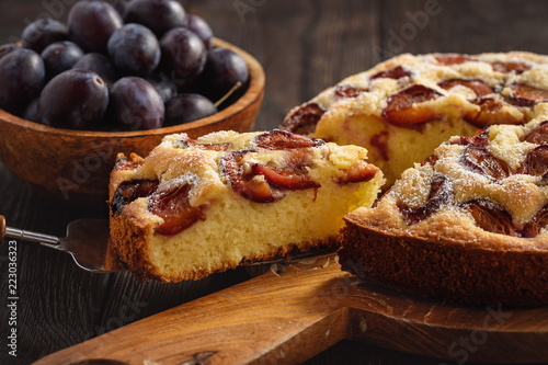Homemade plum cake on dark wooden background.