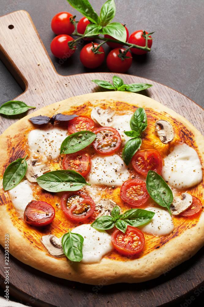 Italian pizza with tomatoes, mozzarella and basil