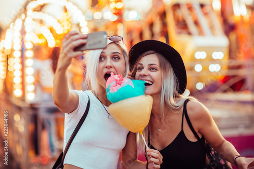 Poster Attraction parc Happy female friends in amusement park eating cotton candy and taking selfie.Two young women enjoying a day at amusement park.