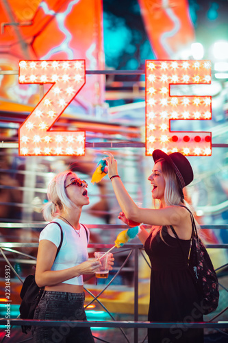 Poster Amusementspark Happy female friends in amusement park eating cotton candy. Two young women enjoying night at amusement park.