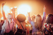 canvas print picture Back view of group of female friends at music festival drinking beer and dancing